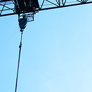 view from below of a blue metal crane with blue sky in the background