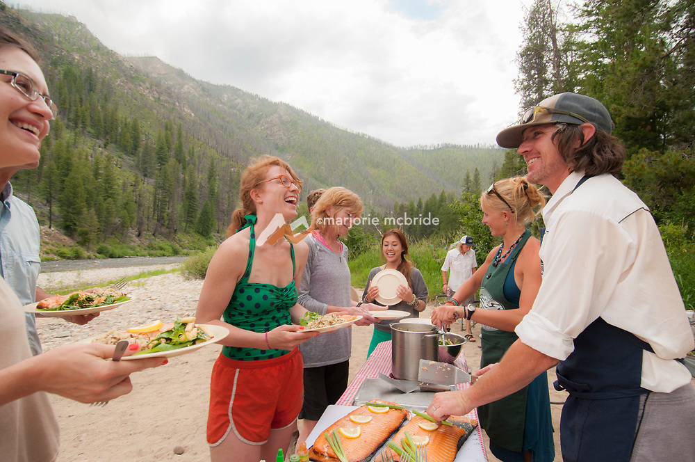 Laughter around the serving table at Sheepeater Camp, Middle Fork of the Salmon River, Idaho.