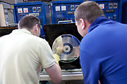Male workers checking and testing vinyl test disk records with a chemical process, factory production line. The Vinyl Factory is the old EMI vinyl works in Uxbridge, Middlesex, producing limited edition vinyls of new releases, plus re-presses of classics. They also act as a distributor of vinyl releases.