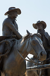 statue of two cowboys holding hands outdoors
