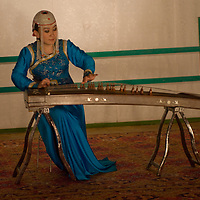 A musician in the famous Mongolian dance and musical troupe, Tumen Ekh, plays a traditional zither called a yatga.