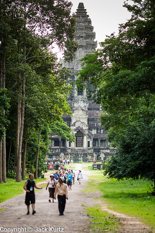 """01 JULY 2013 - ANGKOR WAT, SIEM REAP, SIEM REAP, CAMBODIA:  Angkor Wat as seen from the east gate with tourists on the footpath in front of the temple. Angkor Wat is the largest temple complex in the world. The temple was built by the Khmer King Suryavarman II in the early 12th century in Yasodharapura (present-day Angkor), the capital of the Khmer Empire, as his state temple and eventual mausoleum. Angkor Wat was dedicated to Vishnu. It is the best-preserved temple at the site, and has remained a religious centre since its foundation– first Hindu, then Buddhist. The temple is at the top of the high classical style of Khmer architecture. It is a symbol of Cambodia, appearing on the national flag, and it is the country's prime attraction for visitors. The temple is admired for the architecture, the extensive bas-reliefs, and for the numerous devatas adorning its walls. The modern name, Angkor Wat, means """"Temple City"""" or """"City of Temples"""" in Khmer; Angkor, meaning """"city"""" or """"capital city"""", is a vernacular form of the word nokor, which comes from the Sanskrit word nagara. Wat is the Khmer word for """"temple grounds"""", derived from the Pali word """"vatta."""" Prior to this time the temple was known as Preah Pisnulok, after the posthumous title of its founder. It is also the name of complex of temples, which includes Bayon and Preah Khan, in the vicinity. It is by far the most visited tourist attraction in Cambodia. More than half of all tourists to Cambodia visit Angkor.      PHOTO BY JACK KURTZ"""