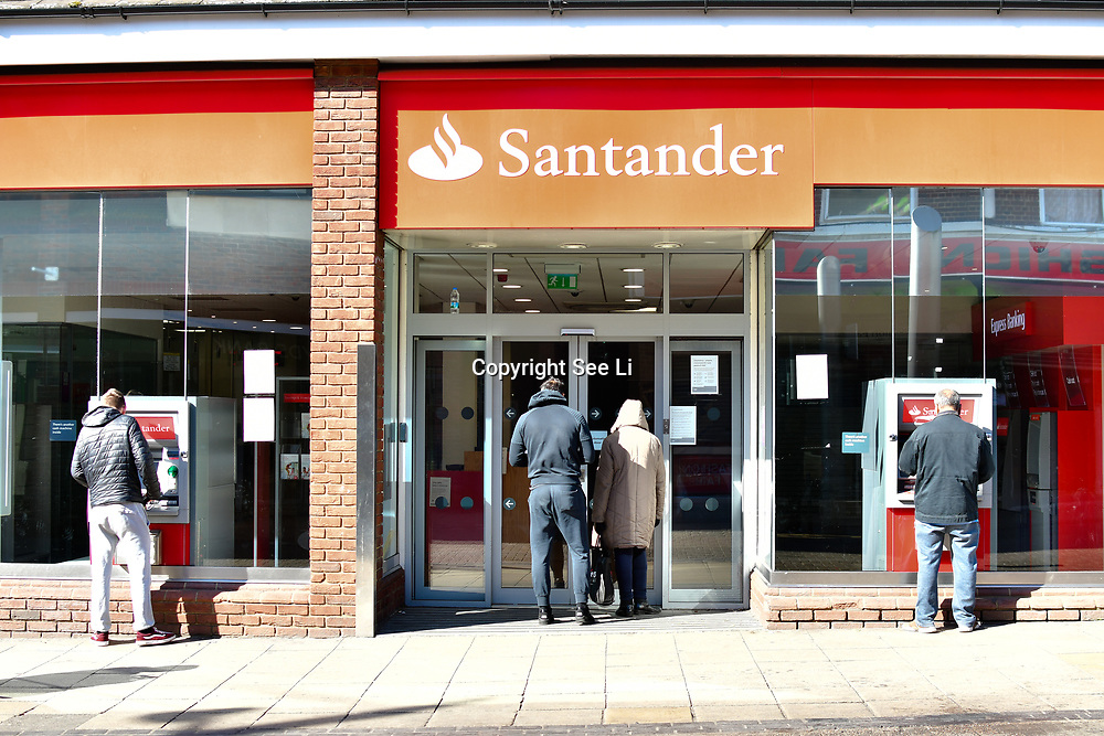 Coronavirus threat - People queue outside Santander Bank only allow one at a time to entry bank, on 23 March in Walthamstow, London, UK.