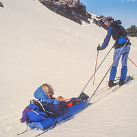 Peter Metcalf family skis with their daughterin a sled near Tom's Place, CA