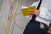Official NYC shield belonging to Investigative Engineering Services, Assistant Commissioner Tim Lynch inspecting a new construction site in Manhattan, New York City. A detail of his department badge and notebook, he inspects new yellow-coded wiring. Tim works in the prevention of damage to old and ensuring new buildings are up to standard plus often, assessing the status of a collapsed structure. From the chapter entitled 'The Skyline' and from the book 'Risk Wise: Nine Everyday Adventures' by Polly Morland (Allianz, The School of Life, Profile Books, 2015). <br /> ,