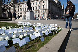 © Licensed to London News Pictures. 22/03/2021. London, UK. A woman stands next to flowers and notes that have been placed in Parliament square in memory to those who lost their lives in the 2017 Westminster Bridge terror attack. Today marks four years since the attack and a commemorative plaque is expected to be installed on Westminster Bridge when Coronavirus restrictions are lifted . Photo credit: George Cracknell Wright/LNP