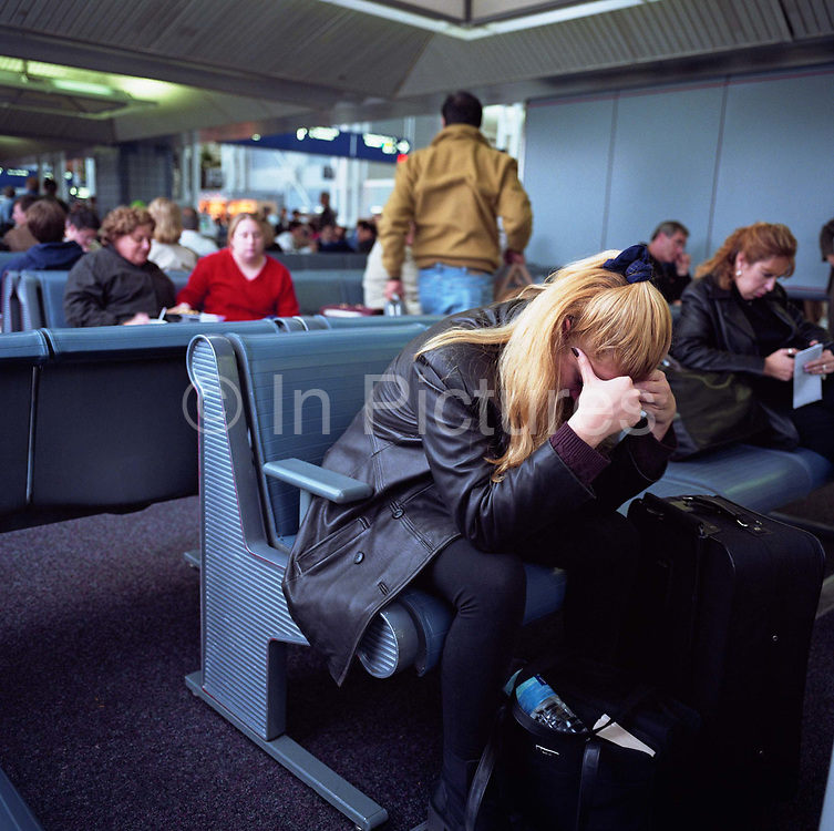 A female passenger leans forward with head in hands amid the busy terminal at Chicago O'Hare Airport, Illinois, USA. Fellow-travellers in the background appear unworried, waiting for their respective flights in a calm manner. The lady in the foreground's body language however, suggests fatigue and distress and perhaps a fear of flying. Picture from the 'Plane Pictures' project, a celebration of aviation aesthetics and flying culture, 100 years after the Wright brothers first 12 seconds/120 feet powered flight at Kitty Hawk,1903.