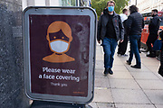 With new local coronavirus lockdown measures now in place and Birmingham currently set at 'Tier 2' or 'high', people wearing face masks near a face mask sign in the city centre on 14th October 2020 in Birmingham, United Kingdom. This is the first day of the new three tier system in the UK which has levels: 'medium', which includes the rule of six, 'high', which will cover most areas under current restrictions; and 'very high' for those areas with particularly high case numbers. Meanwhile there have been calls by politicians for a 'circuit breaker' complete lockdown to be announced to help the growing spread of the Covid-19 virus.