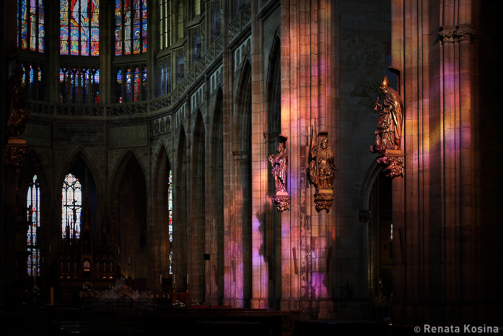 The interior of St. Vitus cathedral in Prague floods with colorful evening sunlight passing through a gothic stainglass window.