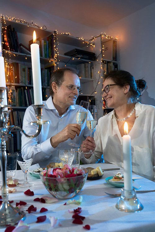 Couple toasting with champagne glasses on candlelight dinner