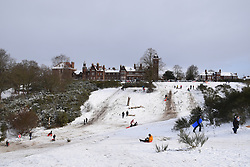 Snow comes to Norwich, UK February 2021 - sledging on Mousehold Heath, Norwich prison in the background