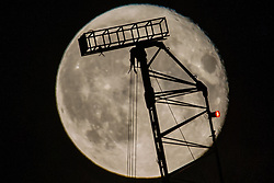 © Licensed to London News Pictures.  26/06/2021. London, UK. The full Strawberry Moon sets behind a crane seen from Hackney Wick, east London. Photo credit: Marcin Nowak/LNP