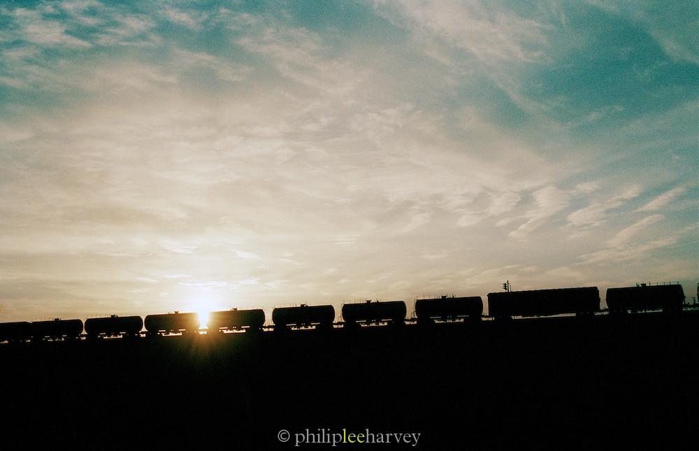 A cargo train moving through barren landscape in China