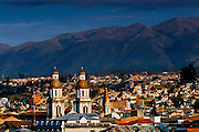 The Andes provide a background for the spires of the colonial Church of Santo Domingo in Cuenca, Ecuador.  The city's center is a UNESCO World Cultural Heritage Trust Site.