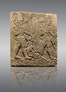 Picture & image of Hittite sculpted Orthostats panel of Long Wall Limestone, Karkamıs, (Kargamıs), Carchemish (Karkemish), 900-700 B.C. Soldiers. Anatolian Civilisations Museum, Ankara, Turkey<br /> <br /> Figure of two helmeted warriors. They have their shield in their back and their spear in their hand. The prisoner in their front is depicted small. A human head is depicted in the left hand of the warrior in the front. The warrior at the rear holds the prisoners sitting on his lap from his hair. Below this figure, which was described small, lies yet another small human figure. <br /> <br /> On a gray background. .<br />  <br /> If you prefer to buy from our ALAMY STOCK LIBRARY page at https://www.alamy.com/portfolio/paul-williams-funkystock/hittite-art-antiquities.html  - Type  Karkamıs in LOWER SEARCH WITHIN GALLERY box. Refine search by adding background colour, place, museum etc.<br /> <br /> Visit our HITTITE PHOTO COLLECTIONS for more photos to download or buy as wall art prints https://funkystock.photoshelter.com/gallery-collection/The-Hittites-Art-Artefacts-Antiquities-Historic-Sites-Pictures-Images-of/C0000NUBSMhSc3Oo