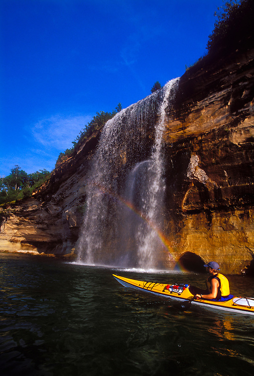 A rainbow is seen in Spray Falls as a sea kayaker explores the coast of Pictured Rocks National Lakeshore near Grand Marais, Mich.