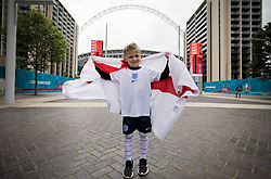 © Licensed to London News Pictures. 07/07/2021. London, UK. 7 year-old Shay holds up an England Flag outside Wembley Stadium ahead of the Euro 2020 semi final between England and Denmark. England are attempting to reach their first final since 1966. Photo credit: Ben Cawthra/LNP