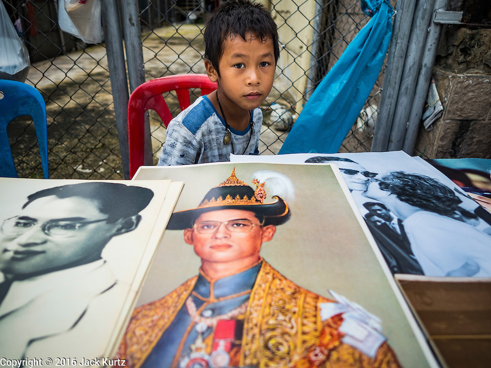 17 OCTOBER 2016 - BANGKOK, THAILAND: A boy sells portraits of Bhumibol Adulyadej, the late King of Thailand, from a table near Sanam Luang in central Bangkok. Thai King Bhumibol Adulyadej died Oct. 13, 2016. He was 88. His death comes after a period of failing health. Bhumibol Adulyadej, was born in Cambridge, MA, on 5 December 1927. He was the ninth monarch of Thailand from the Chakri Dynasty and is also known as Rama IX. He became King on June 9, 1946 and served as King of Thailand for 70 years, 126 days. He was, at the time of his death, the world's longest-serving head of state and the longest-reigning monarch in Thai history.        PHOTO BY JACK KURTZ