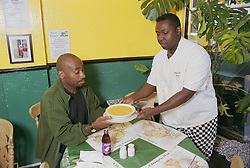 Staff member working in Caribbean café serving customer,