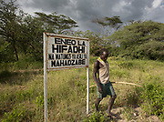 Mokoa in front of signboard indicating the limit of Hadza owned land : no pastoralists and agriculturalists are allowed beyond that point. At and near the Hadza camp of Mahiya.