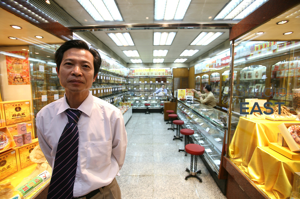 MACAU, CHINA - February 20: A shop owner poses for a photograph on February 20, 2008 in Macau, China. (Photo by Lucas Schifres/Getty Images)
