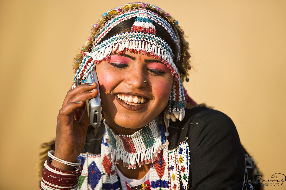 A Kalbelia girl in the Thar Desert dressed in a trial sari, laughing and talking on a cell phone, Thar Desert, Rajasthan, India