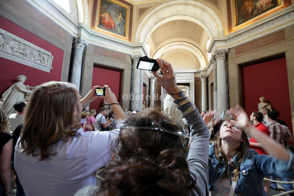 young tourists photographing inside the Vatican museum