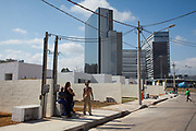 Residents who stayed on move into their new Government built homes, with the Olympic park shining in the background. Vila Autodromo favela, in the west zone of Rio, is in direct site of the Rio 2016 Olympic park. There has been an ongoing struggle between residents and the City Government of Eduardo Paes. After a long battle, 20 families who held on were allowed to stay, on the provision that they moved into houses constructed by the state, in the same style as the public housing programme.