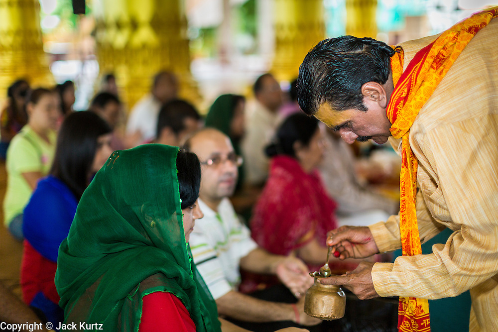 """15 SEPTEMBER 2013 - BANGKOK, THAILAND: A Hindu priest places prasad (an offering) in the hands of a woman on the last day of Ganesha Chaturthi celebrations at Shiva Temple in Bangkok. Ganesha Chaturthi is the Hindu festival celebrated on the day of the re-birth of Lord Ganesha, the son of Shiva and Parvati. The festival, also known as Ganeshotsav (""""Festival of Ganesha"""") is observed in the Hindu calendar month of Bhaadrapada. The festival lasts for 10 days, ending on Anant Chaturdashi. Ganesha is a widely worshipped Hindu deity and is revered by many Thai Buddhists. Ganesha is widely revered as the remover of obstacles, the patron of arts and sciences and the deva of intellect and wisdom. The last day of the festival is marked by the immersion of the deity, which symbolizes the cycle of creation and dissolution in nature. In Bangkok, the deity (statue) was submerged in the Chao Phraya River.     PHOTO BY JACK KURTZ"""