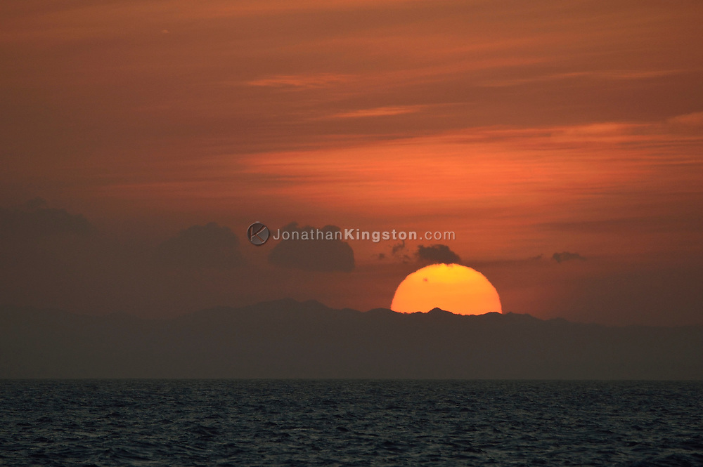 Sunset over the mountains of Panama from the Pacific Ocean.