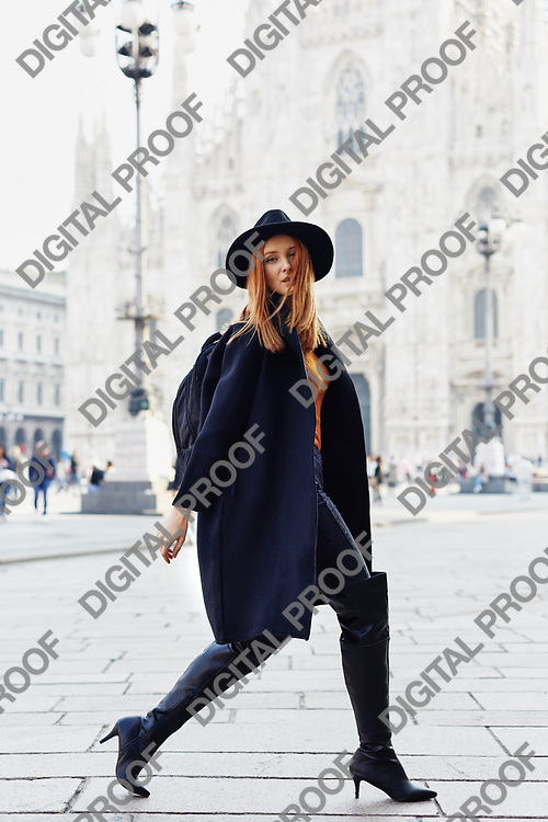 Fashion model walking by the Duomo of Milan looking into the camera wearing a hat and a dark coat and a backpack in a October morning