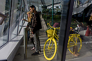 Visitors admire the London skyline from the Sky Garden of the Walkie Talkie building in the City of London. Seen through the outer plate glass window, we see a couple inside enjoying the panoramic view alonside a yellow bicycle 20 Fenchurch Street is a commercial skyscraper in London that takes its name from its address on Fenchurch Street, in the historic City of London financial district. It has been nicknamed The Walkie-Talkie because of its distinctive shape. Construction was completed in spring 2014, and the top-floor 'sky garden' was opened in January 2015. The 34-storey building is 160 m (525 ft) tall, making it the fifth-tallest building in the City of London. Designed by architect Rafael Viñoly and costing over £200 million.