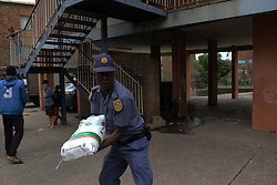 Apr 9, 2020 - Pretoria, Gauteng, South Africa - A South African Police officer help to off load the food hampers at Proclamation hill flat Pretoria South Africa on 09th April 2020 (Credit Image: © Manash Das/ZUMA Wire/ZUMAPRESS.com)