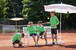 Group of young boys relaxing on tennis court, Bavaria, Germany