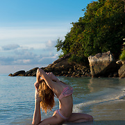 Pigeon pose by a girl practicing beach yoga in Koh Lipe, Thailand