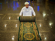 14 JUNE 2017 - BANGKOK, THAILAND: A man rolls up a carpet used in Masjid Hidayatun Islam during Ramadan Iftar. Iftar is the evening meal when Muslims end their daily Ramadan fast at sunset. Iftar is a communal event at Masjid Hidayatun Islam and more than a hundred people usually attend the meal.       PHOTO BY JACK KURTZ