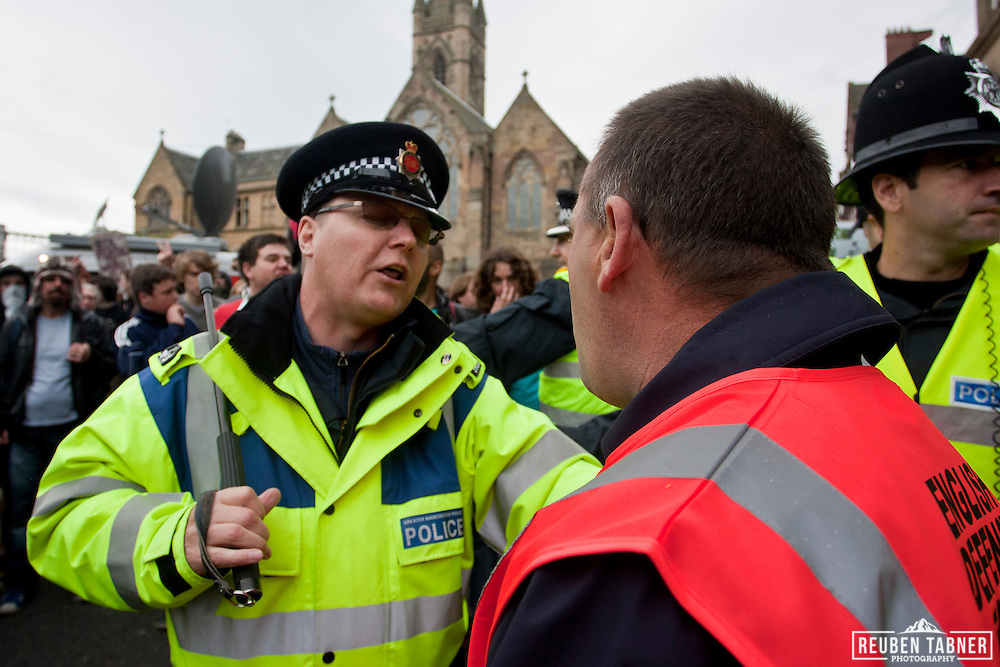 Police hold back a member of the English defence League (EDL) from members of the UAF.