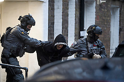 **2018 Pictures of the year by London News Pictures**<br /> © Licensed to London News Pictures. 19/11/2018. London, UK. A man being detained by police during a raid by a CT-SFO (Counter Terrorist Specialist Firearms Officer) unit at a residential block of flats in Westminster, London. A number of men were detained at the scene. Photo credit: Ben Cawthra/LNP