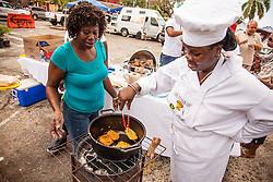 Shirley Honore, right, prepares saltfish cakes, with sister Margret Prosper.  Coal Pot Cook-Off  at Emancipation Garden raising funds for St. Thomas Historical Trust.  St. Thomas, VI.  19 May 2015.    © Aisha-Zakiya Boyd