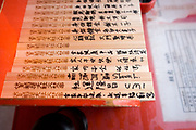 Visitors their names write blessings on pieces of wood in hopes of their dreams coming true.