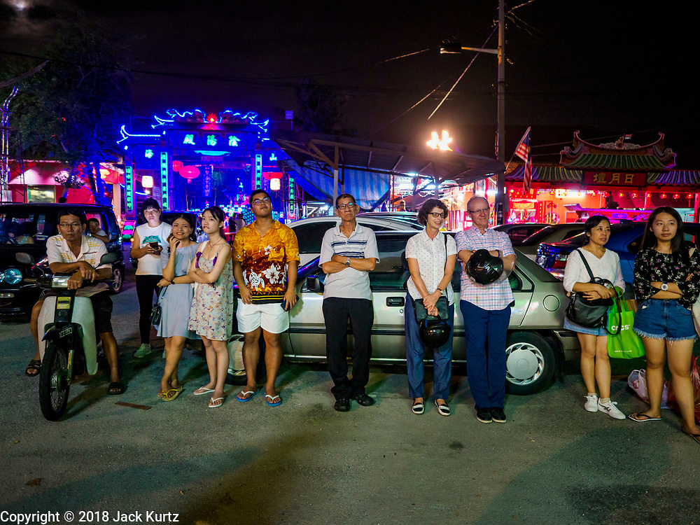 26 AUGUST 2018 - GEORGE TOWN, PENANG, MALAYSIA: People watch a Hokkien style Chinese opera on the Lim Jetty in George Town for the Hungry Ghost Festival. The opera troupe came to George Town from Fujian province in China. The Hungry Ghost Festival is a traditional Buddhist and Taoist festival held in Chinese communities throughout Asia. The Ghost Festival, also called Ghost Day, is on the 15th night of the seventh month (25 August in 2018). During the Hungry Ghost Festival, the deceased are believed to visit the living. In many Chinese communities, there are Chinese operas and puppet shows and elaborate banquets are staged to appease the ghosts.     PHOTO BY JACK KURTZ