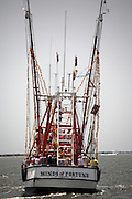 Shrimp boats parade during the Blessing of the Fleet festival in Mount Pleasant, SC. The blessing marks the beginning of the shrimping season, a major industry for coastal South Carolina known as the lowcountry