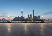 View of the futuristic architecture and the skyline of the buildings of Lujiazui under a moody sky at sunrise from the Bund promenade, Shanghai, China