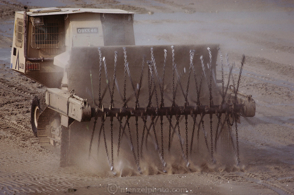 An Aardvark, a gyro guided minesweeper, combing the beach for mines. Huge amounts of munitions were abandoned in Kuwait by retreating Iraqi troops in February, 1991. Also, nearly a million land mines were deployed on the beaches and along the Saudi and Iraqi border. In addition, tens of thousands of unexploded bomblets (from cluster bombs dropped by Allied aircraft) littered the desert. July 1991.