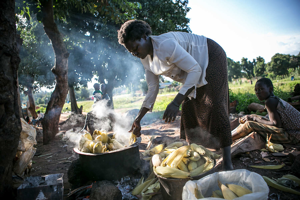 Harriet picks out maize from the pot after boiling them for about two hours before selling them. Harriet was abducted by LRA at the age of eight in Wiiagwem village in Lira District, and spent 13 years in the bush as a girl soldier and a sex slave. she said her husband, a captain in charge, had four wives. She gave birth to two children in the bush and later had six more from the new husband. The new husband rarely stays with her. She sells boiled corns to support herself and children.