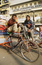 Men with cycle rickshaws waiting for custom outside a bank in India,