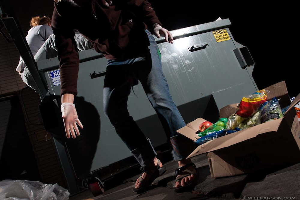 Freegans Elizabeth Latham and Madison Jablonski-Sheffield salvage edible food from a grocery store dumpster in San Diego, California.  Freeganism is a movement based on limited participation in the conventional economy and minimal consumption of resources.