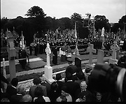 Funeral of Eamon DeValera.   (J72)..1975..02.09.1975..09.02.1975..2nd September 1975..Today saw the funeral of Eamon DeValera. He was laid to rest beside his wife Sinead in Glasnevin Cemetery,Dublin. Dignitries from all around the world attended at the funeral...Mourners are pictured at the grave side awaiting the arrival of the cortege.