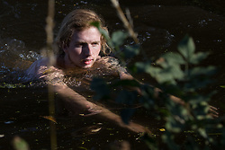 An anti-HS2 activist swims in the Grand Union Canal to halt tree felling works alongside HOAC lake in connection with the HS2 high-speed rail link on 21 September 2020 in Harefield, United Kingdom. Anti-HS2 activists continue to try to prevent or delay works for the controversial £106bn HS2 high-speed rail link on environmental and cost grounds from a series of protection camps based along the route of the line between London and Birmingham.