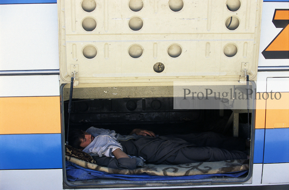 A  driver sleeping in the trunck of the bus.